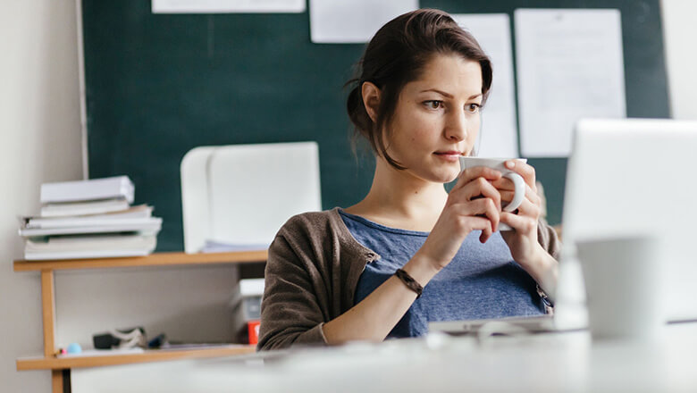 woman holding mug on laptop